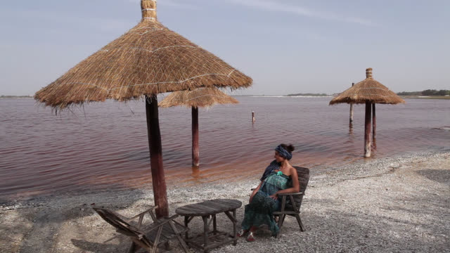 woman in front of the pink lake in senegal - senegal stock videos & royalty-free footage