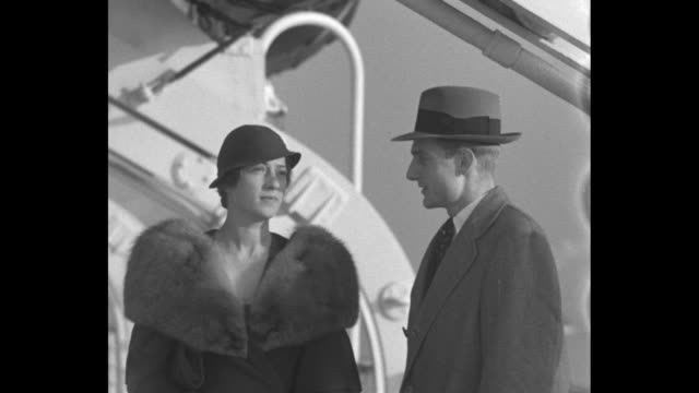 VS woman in fur coat and cloche hat and man in overcoat and fedora walking and posing on deck of ship [exact year not known]