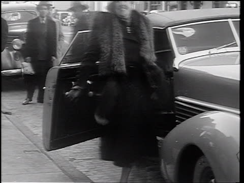 B/W 1937 woman in fur stole exiting car carrying Dachshund by luggage strap on back / newsreel