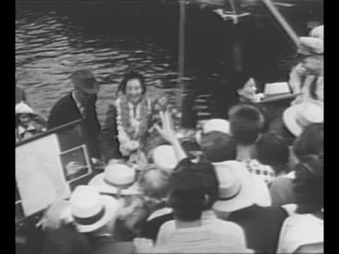 woman in garlanded bodysuit hands bouquet of flowers to us swimmer florence chadwick on her arrival in her hometown of san diego ca / chadwick and... - hometown bildbanksvideor och videomaterial från bakom kulisserna