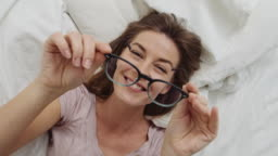 Woman In Glasses Lying In Bed