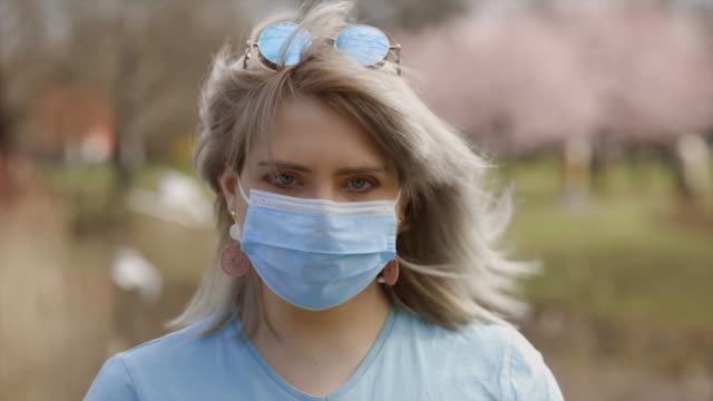 woman in glasses takes off surgical mask in the end of coronavirus pandemic - rimuovere video stock e b–roll