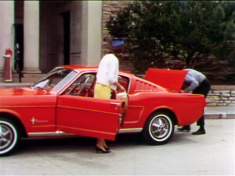 1965 woman in graduation cap standing by Mustang / man taking things out of trunk / industrial