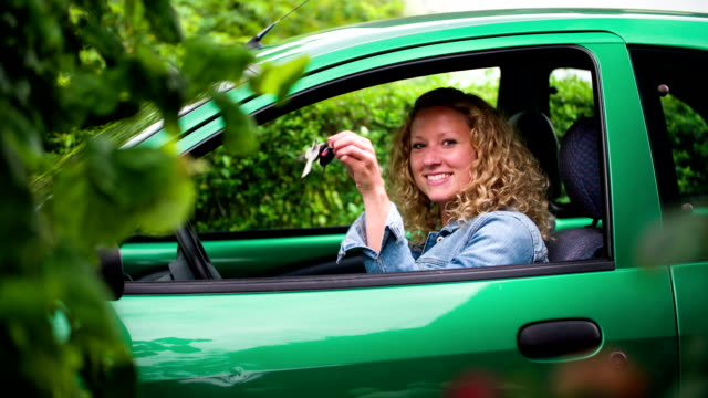 woman in green car showing her car keys - driving test stock videos and b-roll footage