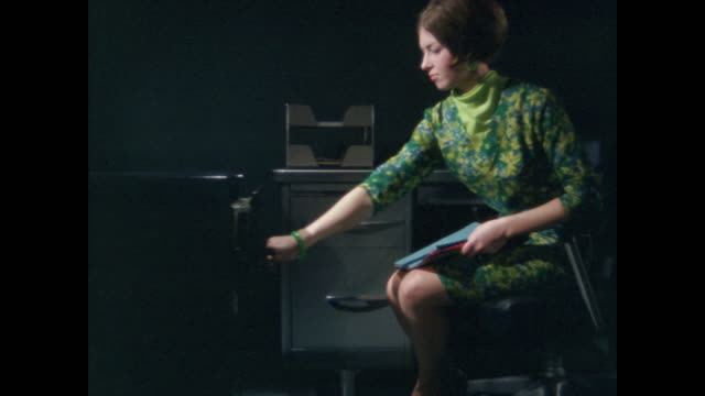woman in green files papers at desk in the dark - filing cabinet stock videos & royalty-free footage