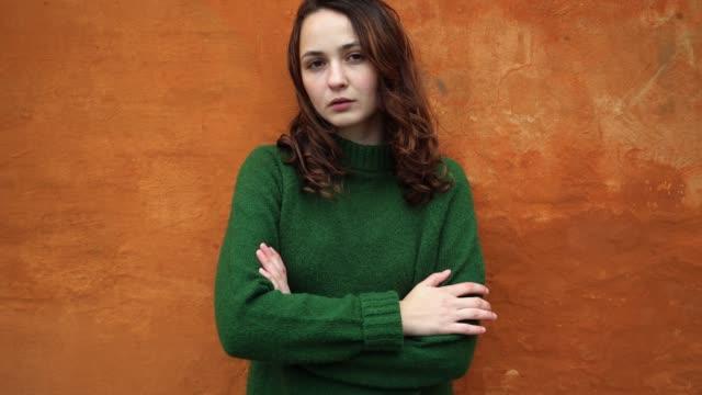 donna in verde più dolce sullo sfondo del muro arancione - serio video stock e b–roll