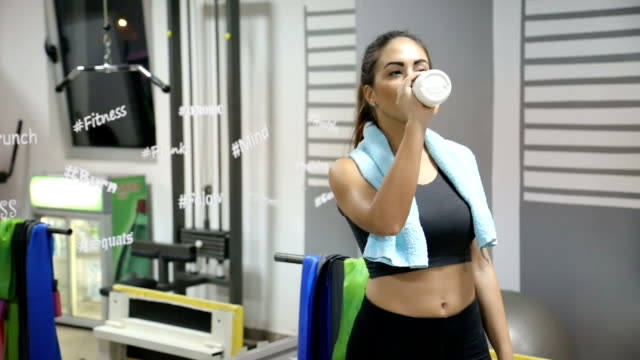 Woman In Gym Drinking Water