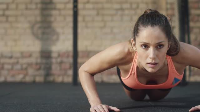 vídeos de stock e filmes b-roll de mulher no ginásio fazendo flexões de braços - flexão de braço