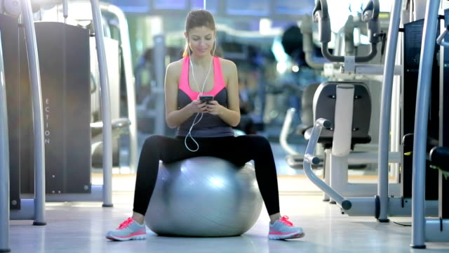 woman in gym sitting on pilates ball - fitness ball stock videos & royalty-free footage