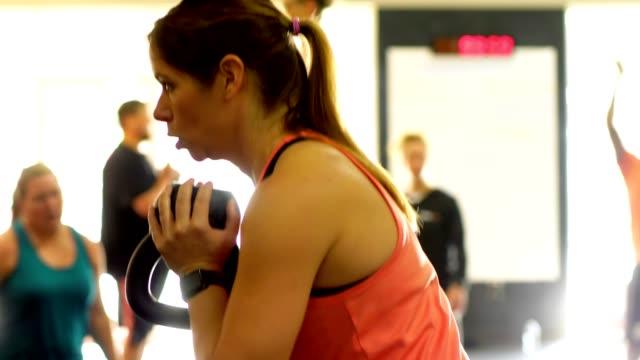 vídeos de stock, filmes e b-roll de mulher no ginásio com kettlebell. - aula de exercícios