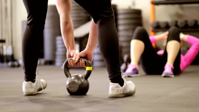 Woman in gym with kettlebell.