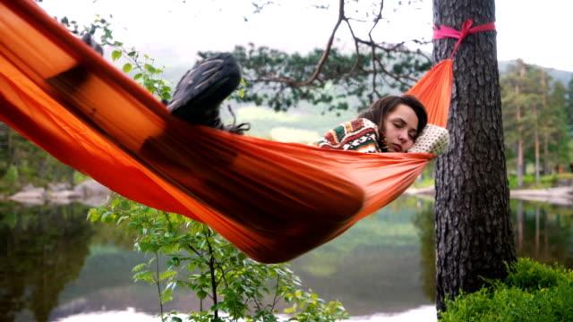 Kvinna i hängmatta i skogen i Norge