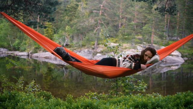 Vrouw in hangmat in bos in Noorwegen