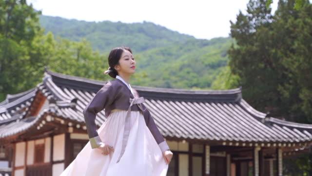 vídeos de stock, filmes e b-roll de woman in hanbok (traditional korean clothing from joseon dynasty) closing her eyes in front of traditional korean house - armação de janela