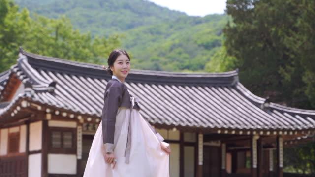vídeos de stock, filmes e b-roll de woman in hanbok (traditional korean clothing from joseon dynasty) in front of traditional korean house - armação de janela