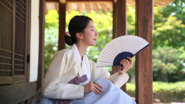 woman in hanbok (traditional korean clothing from joseon dynasty) sitting on daecheongmaru (korean traditional wooden floor porch) and fanning herself - traditional clothing stock videos & royalty-free footage