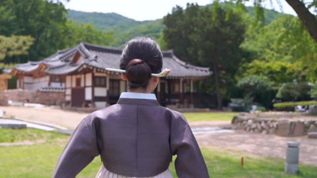 vídeos de stock, filmes e b-roll de woman in hanbok (traditional korean clothing from joseon dynasty) strolling the yard of traditional korean house - coque cabelo para cima