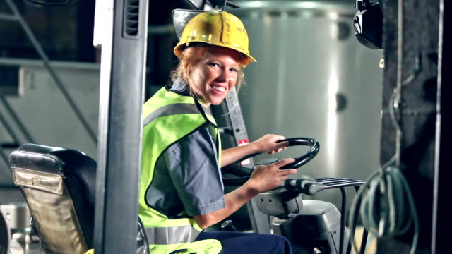 vídeos de stock e filmes b-roll de woman in hardhat and safety vest climbs onto forklift - óculos de proteção