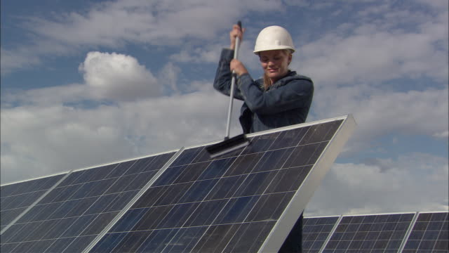 vídeos de stock, filmes e b-roll de la ms ds woman in hardhat cleaning solar panels  / las vegas, nevada, usa - jaqueta jeans