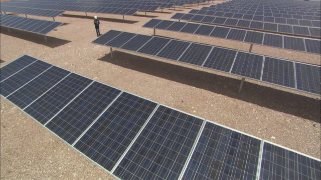 vídeos de stock, filmes e b-roll de ha ws woman in hardhat walking past rows of solar panels  / las vegas, nevada, usa - jaqueta jeans