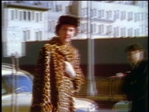 1957 woman in hat + leopard spotted faux-fur coat walking on city sidewalk - coat stock videos & royalty-free footage