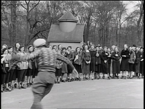B/W 1934 woman in hat roller skating in front of crowd of girls / Belle Isle, Michigan / newsreel