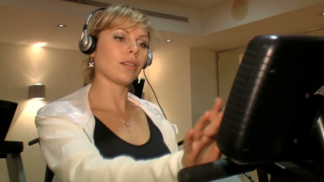 vídeos y material grabado en eventos de stock de mujer en auriculares en gimnasio exersises en bicicleta fija - corredora de footing