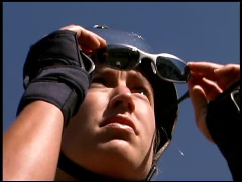 Woman in helmet putting on sunglasses