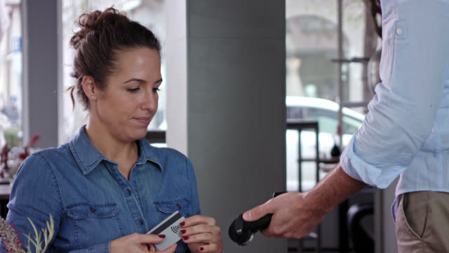 vídeos y material grabado en eventos de stock de woman in her 30s with brown hair wearing jeans shirt pays her drink with a debit card using wireless technology and near filed communication, male waiter in beige chino and light blue shirt. - mano en la barbilla