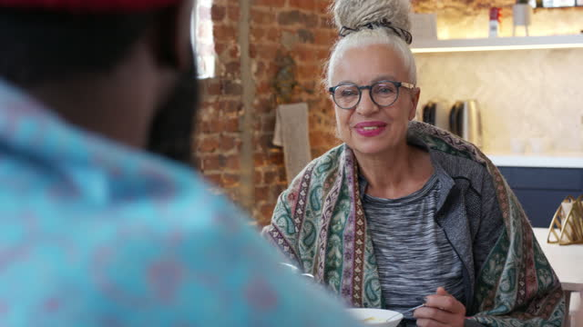 Woman in her 60s smiling and listening to friend at lunch