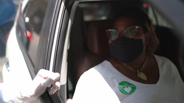 「フイ・ヴァシナド」ステッカーを持つ彼女の車の女性(ポルトガル語で予防接種を受ける)が予防接種を受けている - フェイスマスクを着用 - 絆創膏点の映像素材/bロール