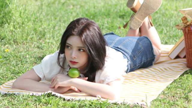 woman in her twenties enjoying vacations while lying down on a picnic mat in the park - 僅年輕女人 個影片檔及 b 捲影像