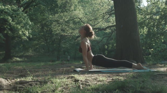 A woman in her twenties practices Yoga in the great outdoors - 4k - slow motion