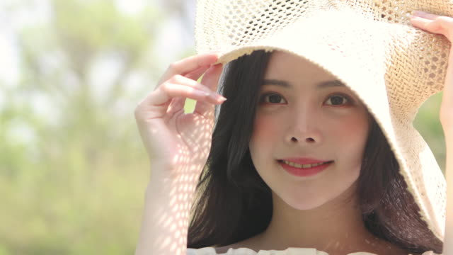 woman in her twenties shielding the sun with a hat and smiling - sun hat stock videos & royalty-free footage