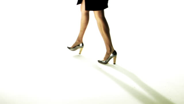 SLO MO, CU, Woman in high heeled shoes and skirt walking in studio, low section