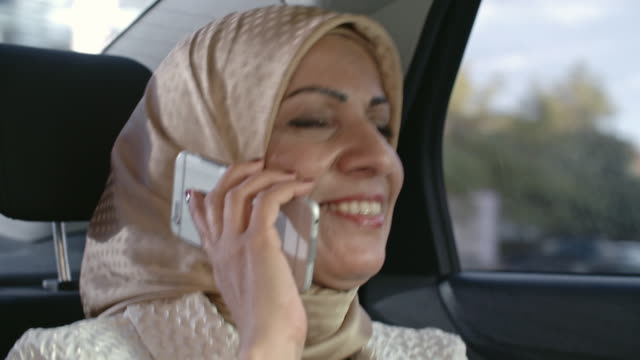 woman in hijab talking on phone in back seat - mid adult stock videos & royalty-free footage
