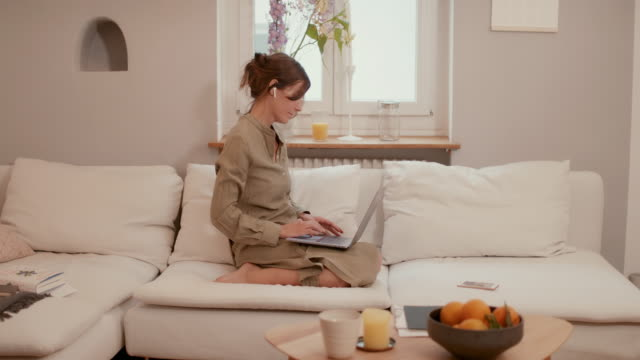 woman in home office on couch with laptop - kneeling stock videos & royalty-free footage