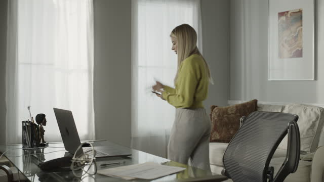 woman in home office talking on cell phone and using laptop / cedar hills, utah, united states - barefoot stock videos & royalty-free footage