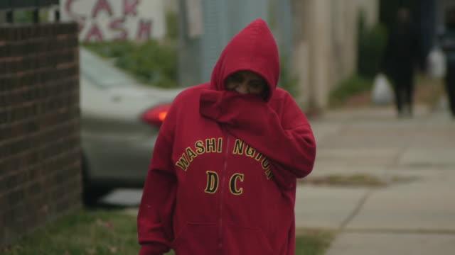 vídeos de stock e filmes b-roll de woman in hooded sweatshirt covers her face on october 28 2012 in washington dc - sweatshirt