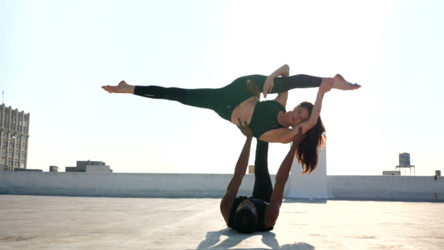 ms woman in inverted splits while supported on dance partners feet while performing on rooftop - tights stock videos & royalty-free footage