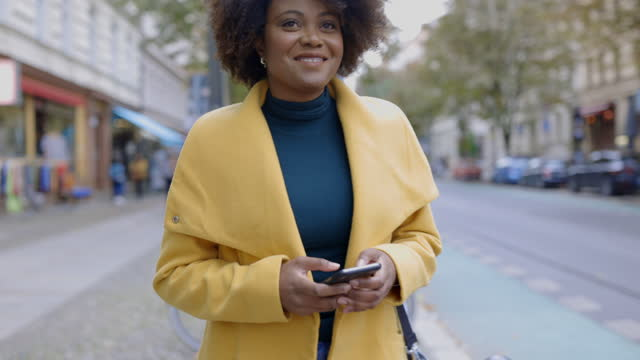 woman in jacket using smartphone on footpath - mid adult women stock videos & royalty-free footage