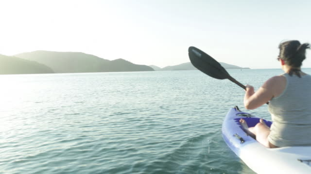 Woman in kayak paddles into shot.