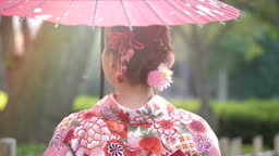 Woman in Kimono holding umbrella and walking on the street