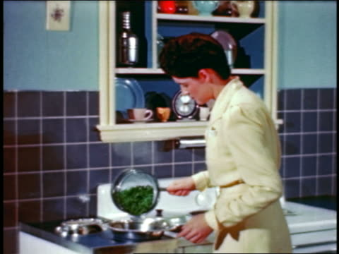 1946 woman in kitchen emptying cooked peas from saucepan into metallic bowl