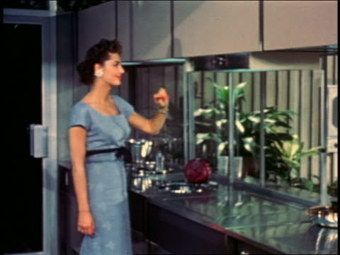 1957 woman in kitchen opening futuristic automatically opening cabinet + oven by waving hand - 1957 stock videos & royalty-free footage