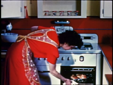 1955 woman in kitchen opening oven + pulling tray from oven