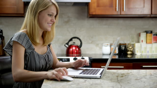 woman in kitchen using laptop - computer mouse stock videos & royalty-free footage