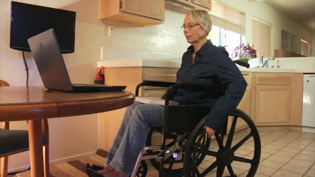 woman in kitchen with laptop computer - persons with disabilities stock videos & royalty-free footage