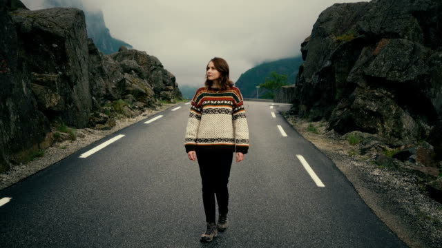 woman in knitted sweater walking on road in mountains in norway - stone material stock videos & royalty-free footage