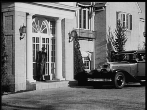 b/w 1928 woman in la salle car pulling up to door of mansion where other woman waits / industrial - 1928 stock-videos und b-roll-filmmaterial
